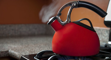A red-orange kettle heating on a stove with steam rising out of the spout