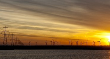 Wind farms and pylons against a sunset