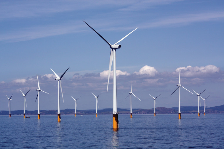 A seascape underneath a blue sky with wind turbines appearing out of the water
