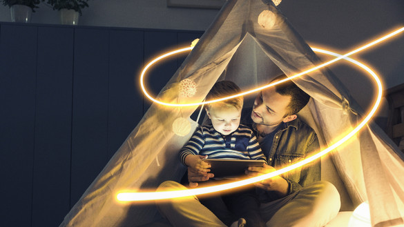 Man and child in tent with tablet