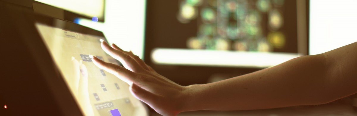 A hand reaching out to tap a touch screen display with screens in the background