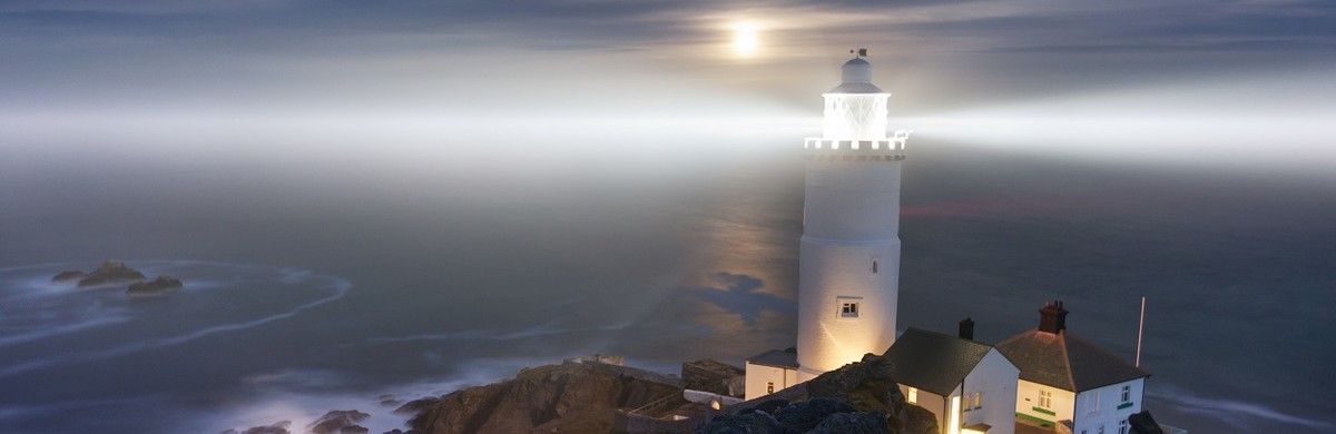 A lighthouse at night on a clifftop for National Grid ESO Distributed ReStart annual conference