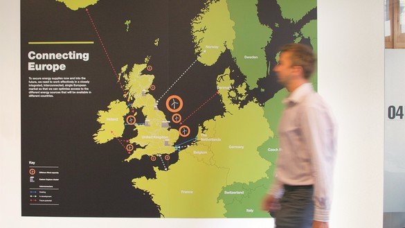 Connecting Europe map on a white wall with someone walking in front of it