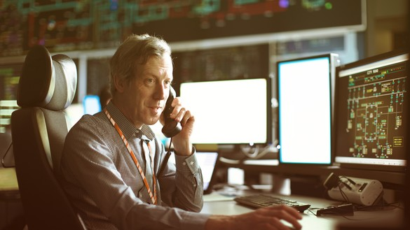 A National Grid worker on the phone surrounded by control room screens