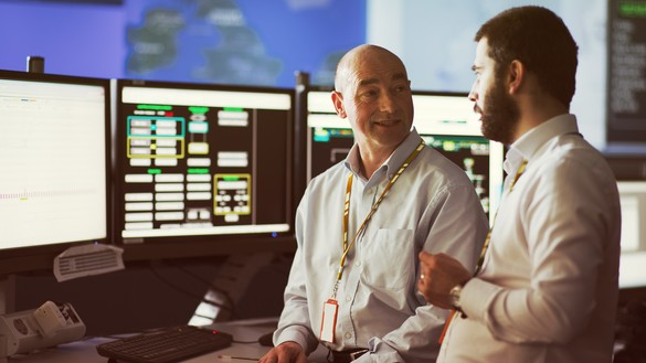 Two National Grid representatives talking with display screens in the background