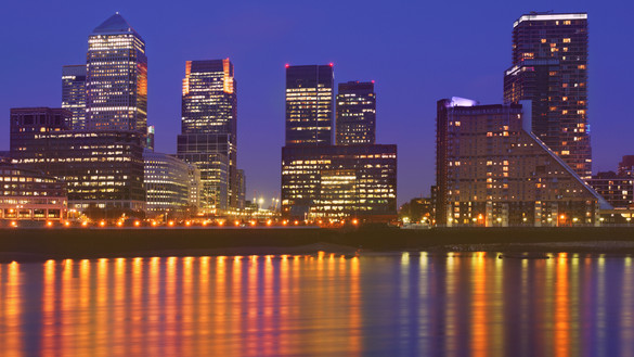 A nighttime view of Canary Wharf with lights reflecting in the waterfront