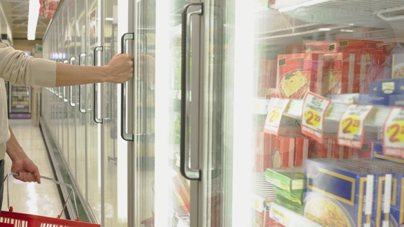 A shot of food inside supermarket freezers with someone reaching to open one of the doors