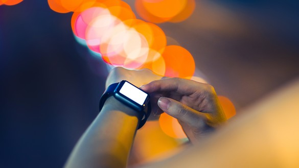 A partial view of an arm with a smart watch around the wrist and out of focus lighting in the background