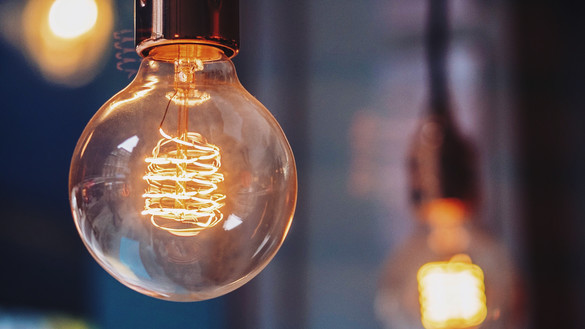 An exposed lightbulb suspended with other lightbulbs blurred in the background