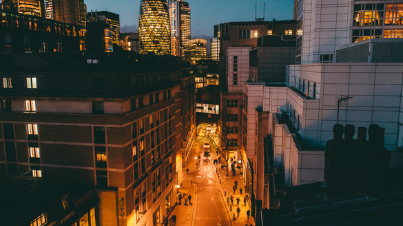 A nighttime view of tall London buildings with a well-lit street running through the middle