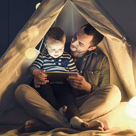 National Grid ESO - Electricity Explained - man and child reading under a tent