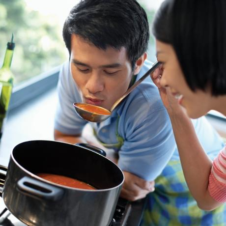 A woman feeding a man a spoonful of sauce from a pan that is heating on the hob with an out of focus kitchen space in the background