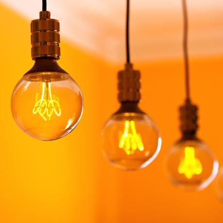 A row of exposed lightbulbs with an orange wall in the background