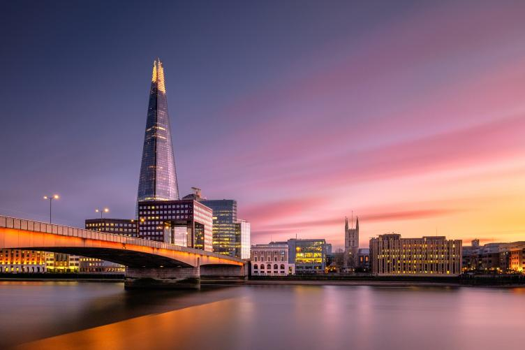 A waterfront view of the London Bridge at dusk with well-lit buildings in the background